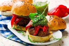 Feta stuffed turkey burgers with arugula pesto and roasted red peppers. Style rustic .selective focus Royalty Free Stock Image