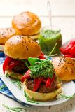 Feta stuffed turkey burgers with arugula pesto and roasted red peppers. Style rustic .selective focus Stock Photos