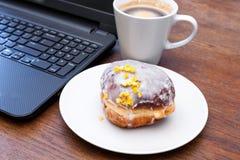 Feta torsdag - munk, kaffe och bärbar dator Fotografering för Bildbyråer