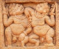 Feta två och lyckligt folk som dansar på stenlättnad av den 7th århundradetemplet i den Badami staden, Indien Arkivbild