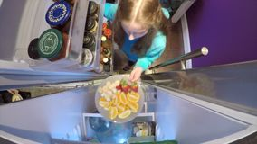 Fetching Fruit from the Fridge. Little girl is opening the fridge at home to get a plate of fruit stock footage