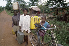 Fetching water by children on endlessly long road. Uganda, Luweero district, village Zirobwe Bungo: group portrait of Ugandan boys have fetched drinking water Stock Images