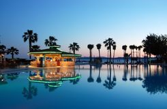 View of the pool, pool bar and palm trees at sunset in Turkish h Royalty Free Stock Photography
