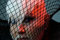 Fetish fashion. Transgender man cover face with fishnet. Male makeup look. BDSM fashion accessory. Heterosexual man with. Male makeup. Drag queen stock images