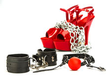Fetish stuff: hand cuffs, mask, whip and extreme high heels shoe. Various fetish stuff for role playing and BDSM: hand cuffs, a ball gag and high heels shoes Stock Photography