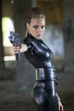 Fetish woman with gun. Young woman in fetish leather suit holding a gun stock photography