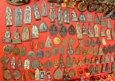 Fetishes Thailand amulets. Popular Buddhist The faith to secure a fortune by trade and hang neck. The red background Stock Photo