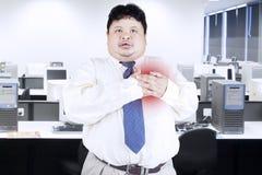 Fetmaaffärsman som får hjärtinfarkt royaltyfri bild