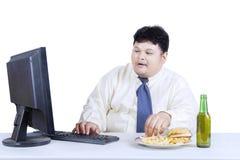 Fetmaaffärsmanarbete, medan äta Arkivfoto