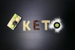 Fett keto-jordnötsmör, ostkaka, matcha klumpa ihop sig te på mörk svart träbakgrund recept för te för för keto-proteinbollar och  arkivfoton