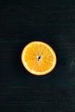 Fetta arancio nel centro della tavola di legno scura Immagine Stock