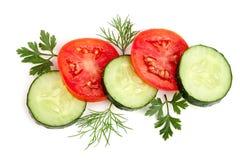 Fetta con le foglie del prezzemolo, aneto del cetriolo e del pomodoro su fondo bianco Vista superiore Fotografia Stock