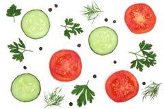 Fetta del cetriolo e del pomodoro con le foglie, l'aneto ed i granelli di pepe del prezzemolo isolati su fondo bianco Vista super Immagine Stock Libera da Diritti