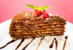 Fetta del dolce di cioccolato con le bacche e le foglie della menta su un piatto, su un fondo rosso Copi lo spazio immagini stock libere da diritti