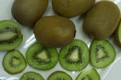 Fetta del kiwi fra i molti intero ` s del kiwi fotografia stock