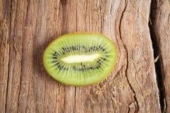Fetta del kiwi isolata su fondo di legno Fotografia Stock Libera da Diritti