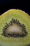 Fetta del Kiwi su priorità bassa nera Immagini Stock