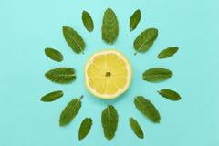 Fetta del limone con le foglie di menta su un fondo verde blu sotto forma di un sole concetto di estate di vista superiore immagini stock libere da diritti