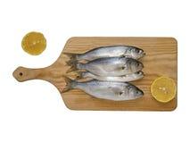 Fetta del limone e del pesce serra sulla fresa di legno con fondo bianco Immagine Stock