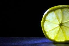Fetta del limone su un fondo nero ad una luce posteriore immagine stock libera da diritti