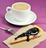 Fetta della torta di formaggio e primo piano della tazza di caffè su fondo porpora Fotografia Stock