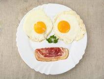 Fetta di bacon con due uova sul piatto come fronte Fotografia Stock