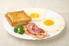 Fetta di bacon con due uova sul piatto con i pani tostati Fotografia Stock Libera da Diritti
