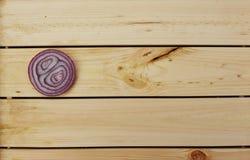 Fetta di cipolla sul ripiano del tavolo di legno Fotografie Stock