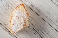 Fetta di dolce con un morso su fondo di legno bianco fotografia stock libera da diritti