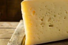Fetta di formaggio di asolo sul bordo di legno su fondo scuro fotografia stock libera da diritti