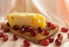Fetta di formaggio di Jarlsberg con l'uva rossa Fotografia Stock