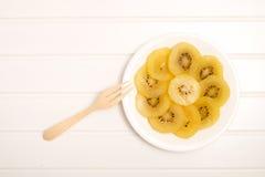 Fetta di kiwi giallo del kiwigold sul piatto Fotografie Stock Libere da Diritti