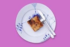 Fetta di lasagne su un piatto con la forcella e sul coltello isolato sopra su fondo rosa Vista superiore fotografia stock