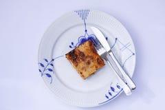 Fetta di lasagne su un piatto con la forcella ed il coltello Immagine di vista superiore fotografia stock