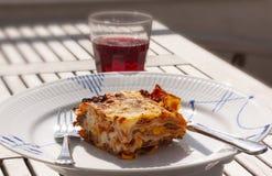 Fetta di lasagne su un piatto e su un bicchiere di vino su una tavola Fine in su fotografia stock libera da diritti