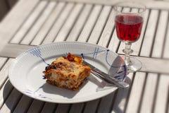 Fetta di lasagne su un piatto e su un bicchiere di vino su una tavola Fine in su fotografie stock