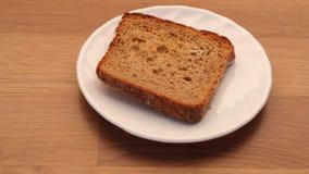 Fetta di pane di segale sul tavolo da cucina del piatto video d archivio