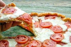 Fetta di pizza con formaggio che allunga a disposizione Immagini Stock Libere da Diritti