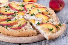 Fetta di pizza con il pollo e di pesche su un bordo di legno Fotografie Stock Libere da Diritti