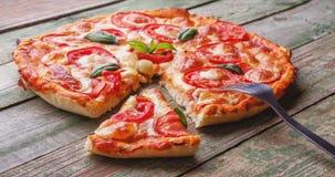 Fetta di pizza con la forcella sulla tavola di legno verde Immagine Stock Libera da Diritti