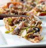 Fetta di pizza con le guarnizioni supreme su una zolla Fotografia Stock