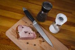 Fetta di prosciutto affumicato su un tagliere Fotografia Stock