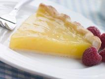 Fetta di torta della cagliata di limone con i lamponi inglesi Fotografia Stock Libera da Diritti