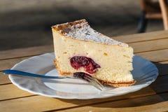 Fetta di torta di formaggio con il materiale da otturazione della ciliegia Fotografia Stock