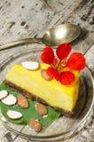 Fetta di torta di formaggio della zucca decorata con i fiori freschi e le mandorle Fotografia Stock