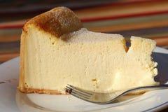 Fetta di torta di formaggio sul piatto bianco con la forcella fotografie stock