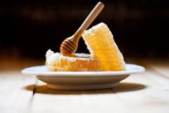 Fetta dolce gialla del favo dell'alimento sano fresco del miele con il piatto bianco del merlo acquaiolo di legno ed il fondo scu fotografia stock