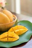 Fetta gialla del mango sulla foglia della banana Fotografie Stock