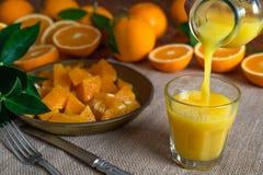 Fette arancio, foglie arancio e vetro di succo d'arancia fresco fotografia stock