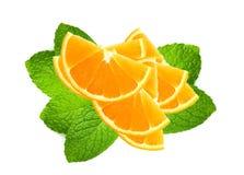 Fette arancio fresche sopra le foglie di menta isolate su bianco Immagine Stock